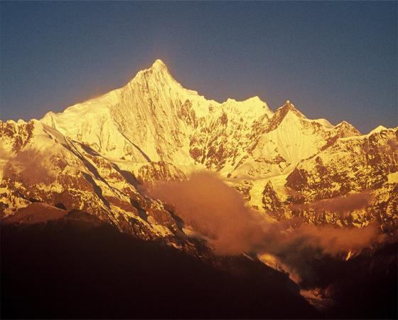 从德钦县沿滇藏公路北上、东行至10公里处的飞来寺,但见澜沧江对岸数百里冰峰接踵、雪峦绵亘,势如刀劈錾斫,气势非凡。这便是名传遐迩的以卡瓦格博峰为中心的梅里雪山。 梅里雪山,北连西藏阿冬各尼山,南与碧落雪山相接,平均海拔在6000米以上的便有10多座、称太子十三峰。那耸立于十三峰之上的卡瓦格博峰,海拔6740米、为云南第一峰。  卡瓦格博峰是藏传佛教的朝拜圣地、传说变尼玛派分支家居巴的保护神,位居藏区八大神山之首,故在当地有巴何洛登地的称号。 卡瓦格博,藏语意为白似雪山之意,俗称雪山之神。传